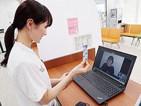 薬を画面向こうの患者に示しながら服薬指導を行う