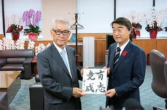 本庶氏(左)が書した色紙が根本大臣に手渡された